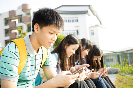 Teenage Students sitting and using smart phone