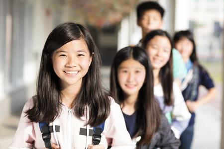 Grupo de estudiantes adolescentes de pie antes del aula