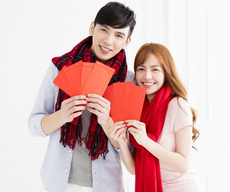 gelukkig Aziatisch paar dat rode envelop voor Chinees nieuw jaar toont