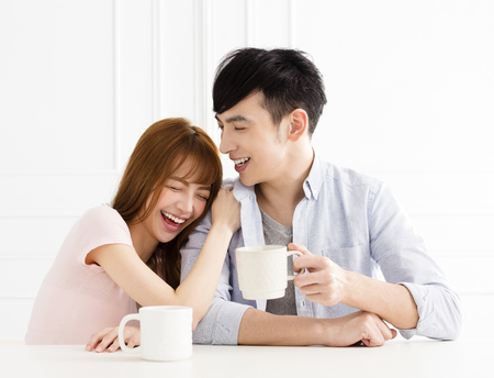 happy couple relaxing together at home with cup of coffee