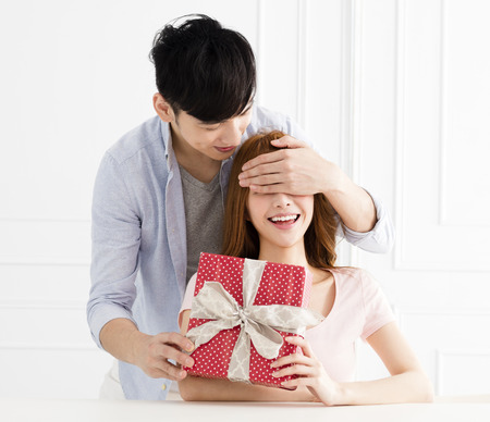 young man surprises his girlfriend with present at home