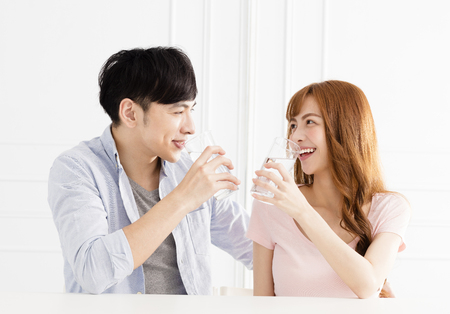 Young couple drinking clean water at home