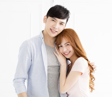 happy young asian couple hugging in living room