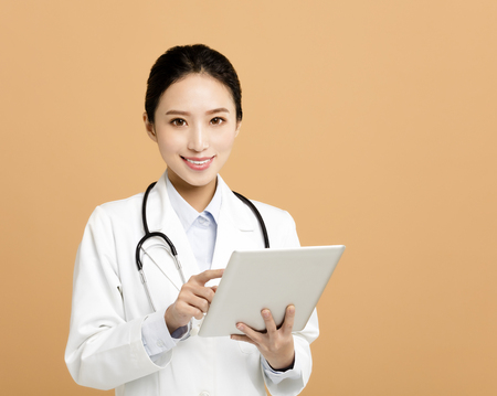 Smiling asian woman pharmacist doctor with tablet  Stock Photo