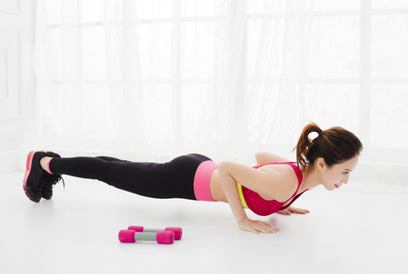 smiling young woman doing push-ups at home Stock Photo