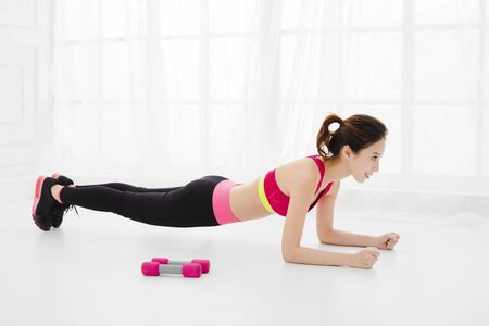 smiling young woman doing push-ups at home
