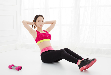 young women doing sit-ups on floor at home