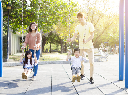 Happy Asian family playing swing together Stockfoto