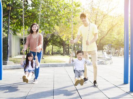 Szczęśliwa azjatycka rodzina gra razem swing