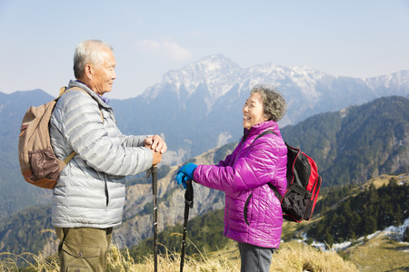 happy senior couple hiking on the mountain 写真素材