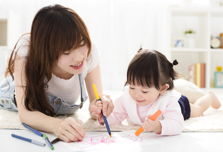 happy Mother and daughter drawing together