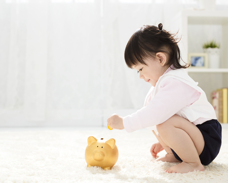 baby girl inserting a coin into piggybank