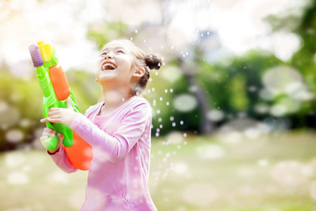 happy little girls playing water guns in the park