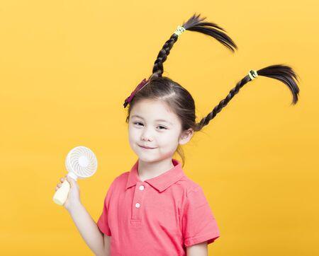 smiling little girl enjoying cool wind from electric fan