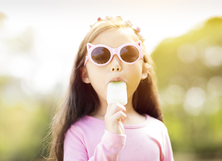 happy little girl eating popsicle at summertime