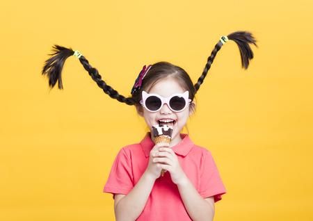 smiling little girl eating ice cream 写真素材