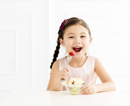 happy little girl eating vegetable salad 