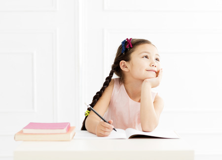 happy little girl  studying and thinking 스톡 콘텐츠
