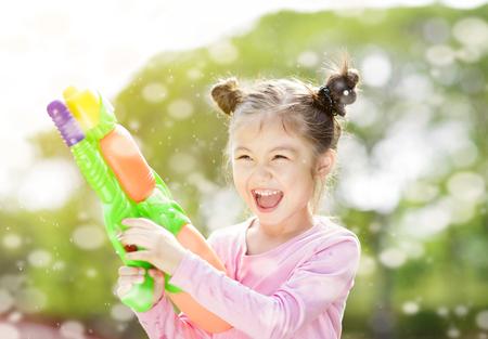 happy little girl playing water guns