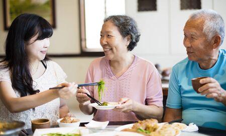 女儿和高级父母在餐厅享用晚餐