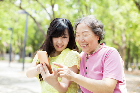 happy senior mother and daughter watching the smart phone