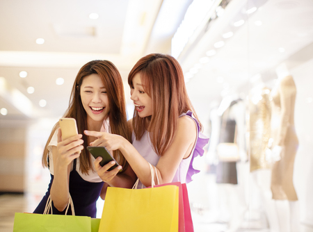 girls watching phone and shopping in the mall Фото со стока - 100466396