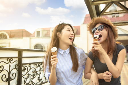 Happy girls enjoy ice cream and summer vacations