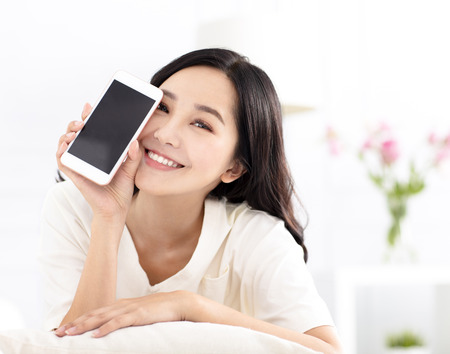 happy woman sitting on couch and showing the phone