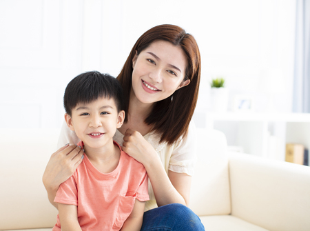 Mother and son smiling on couch  Stockfoto