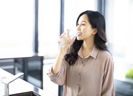 young woman drinking water in the kitchen at home