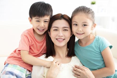 mère et enfants souriants sur le canapé