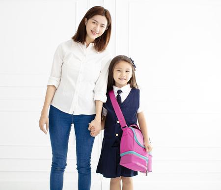 Mère tenant la main de sa fille prête à aller à l'école