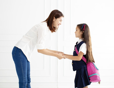 Madre sosteniendo la mano de la hija lista para ir a la escuela