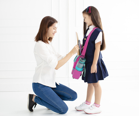 mother and daughter preparing backpack for school 写真素材