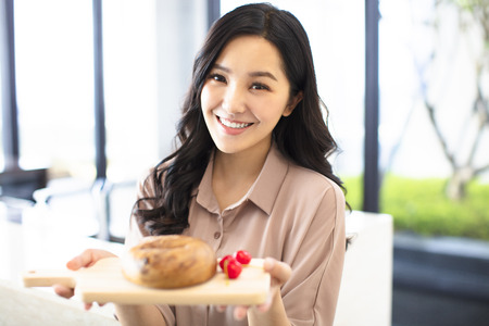 young woman showing bread in kitchen