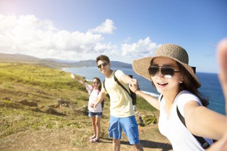 familia feliz tomando selfie en la costa