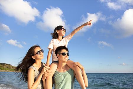 glückliche Familie, die am Strand steht, beobachten den Sonnenuntergang