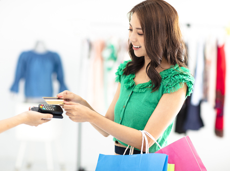 young woman shopping in clothes store and paying by credit card