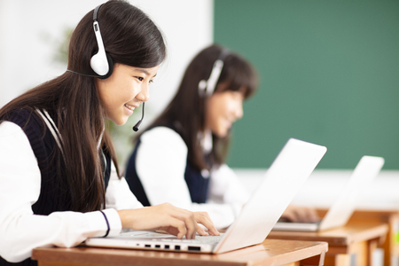 teenager student learning online with headphones and laptop Foto de archivo