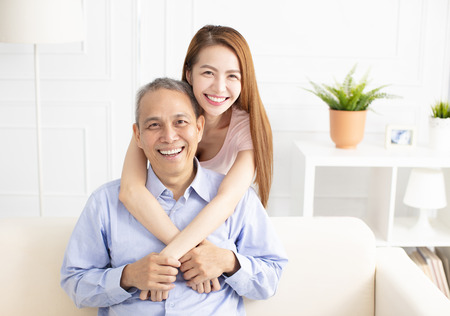 happy asian daughter holding father on sofa