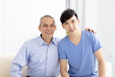 smiling senior father and adult son at home