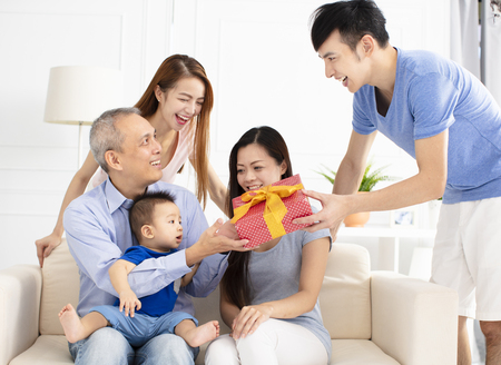 happy family celebrating and giving gift to father
