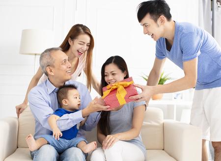 Familia feliz celebrando y dando regalo a padre Foto de archivo - 104018523