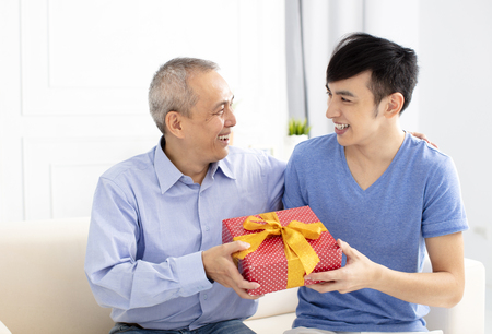 happy family celebrating and son giving gift to father Standard-Bild