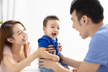 Portrait of young happy family with baby