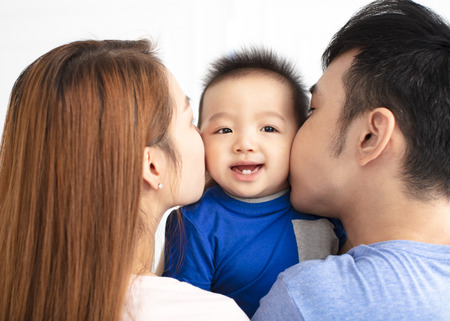 Portrait of young happy family kissing baby
