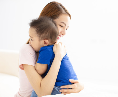 Close Up Of Mother Cuddling Baby son At Home