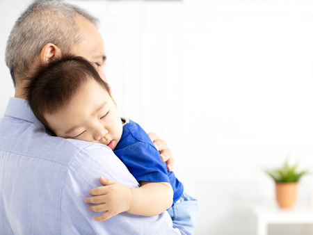Grandfather Holding Sleeping Grandson baby 스톡 콘텐츠 - 105435208