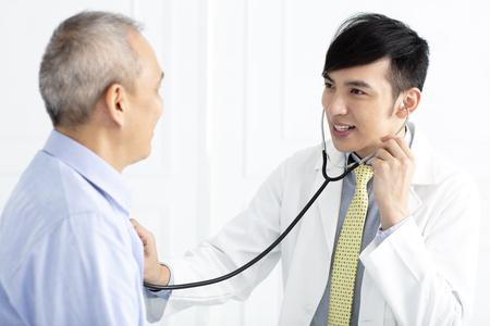 jonge mannelijke arts in gesprek met senior man patiënt