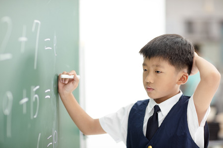 confuse schoolboy try to answer question on chalkboard